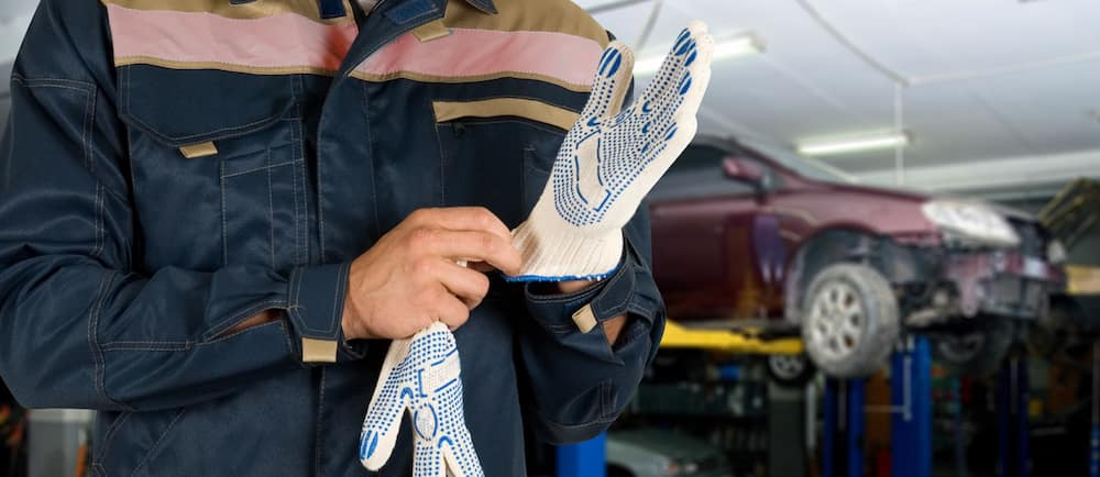 auto mechanic putting on gloves with a car in the background