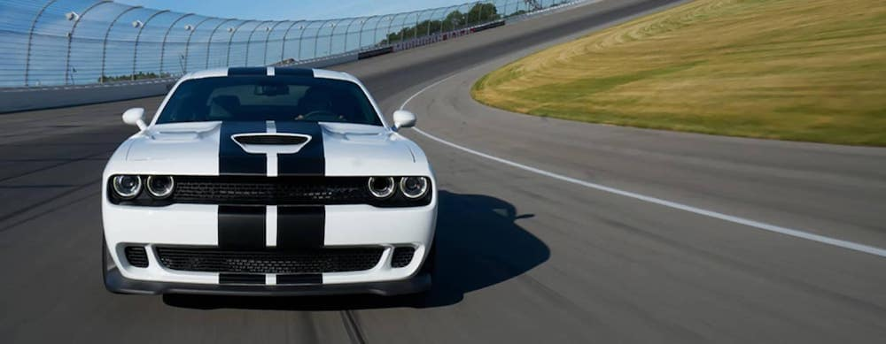 White 2018 Challenger with black racing stripe on a track