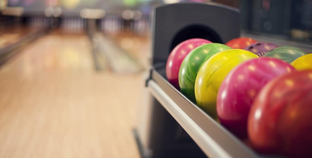 Pink, yellow, and green bowling balls lined up