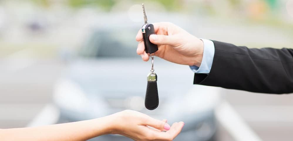 Salesman handing car keys to a person who just bought a car