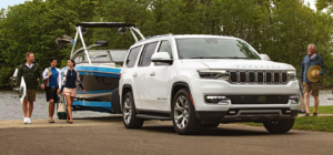 The 2022 Jeep Wagoneer towing a boat next to people getting out of the water.