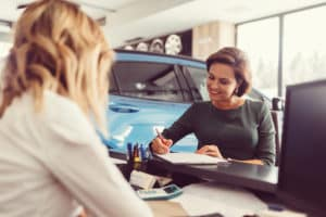 Woman Signing Financing Agreement - Enfield, CT - Artioli Chrysler Dodge Ram