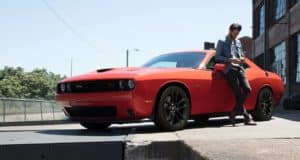 Man leaning against Dodge Challenger muscle car