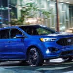 Blue 2020 Ford Edge going around curve