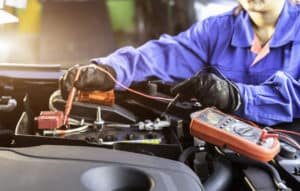 technician measure voltage of battery in the car