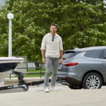 2019 Buick Enclave towing a boat as child runs toward it