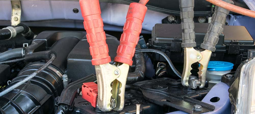Close up of jumper cables attached to a car battery