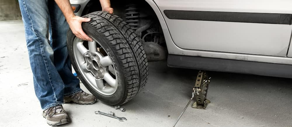 Man removing a front tire from a vehicle