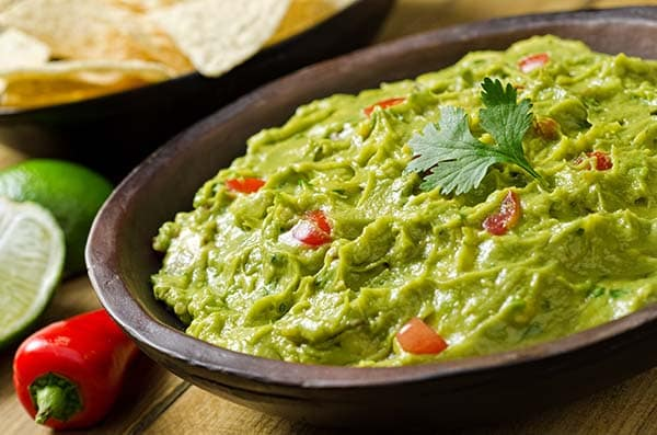A bowl of creamy guacamole dip with peppers, tomato, cilantro, and lime.
