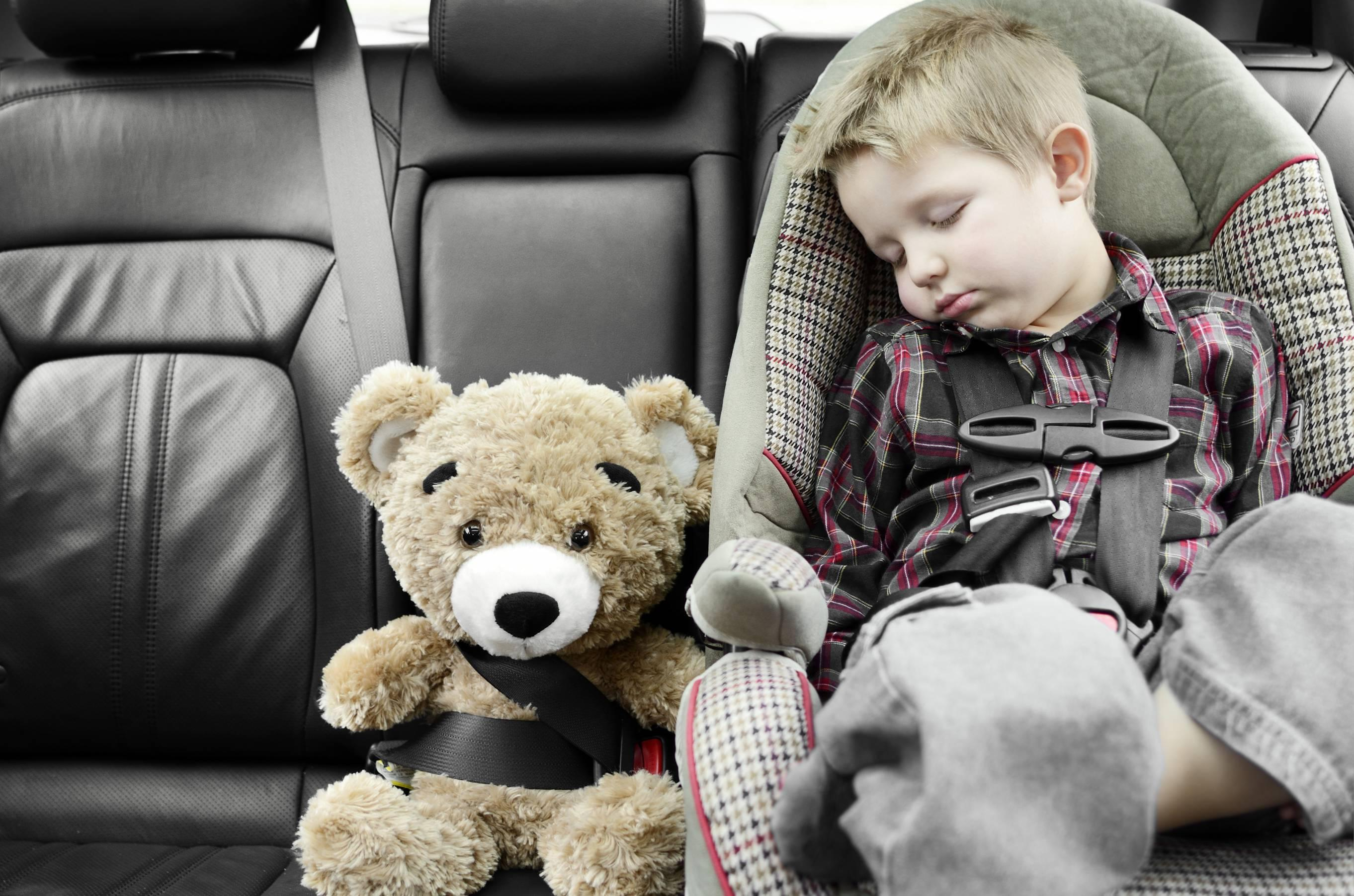 Child asleep in car seat next to teddy bear, car-seat safety