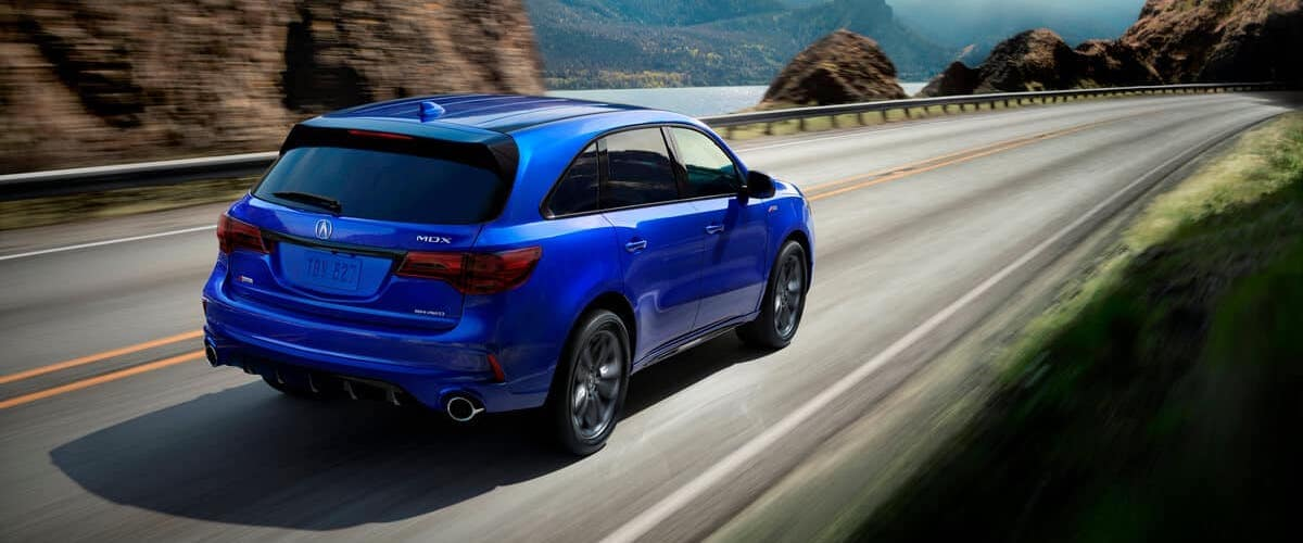 Blue 2020 Acura MDX A-Spec driving through mountain highway