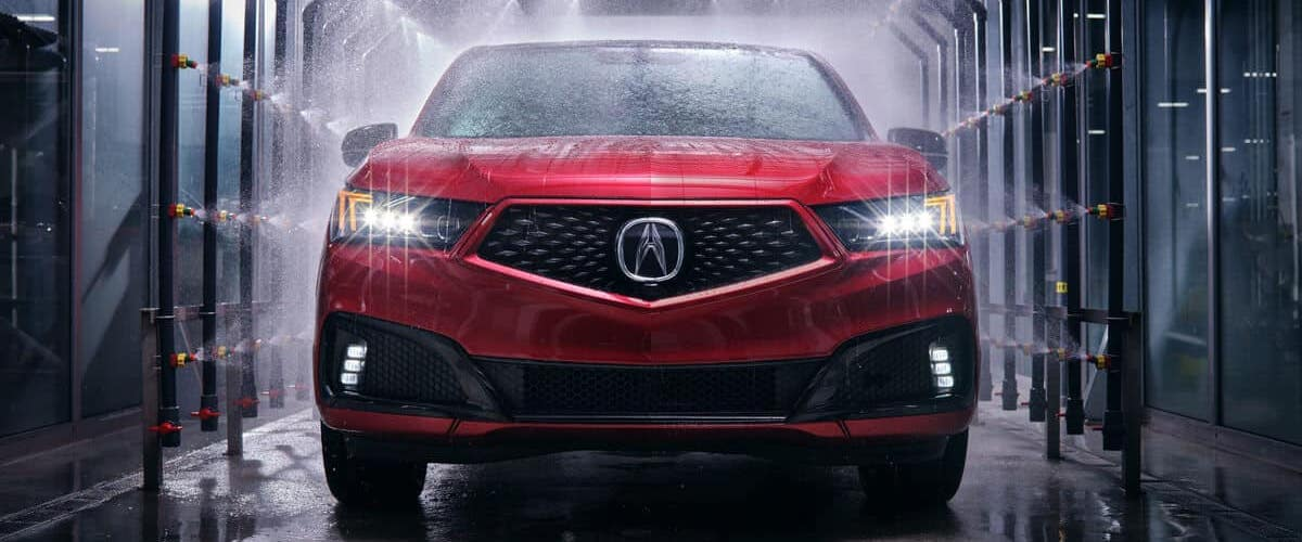 Red 2020 Acura MDX PMC front with water jets spraying on it