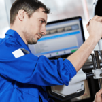 Man in blue shirt performing wheel alignment