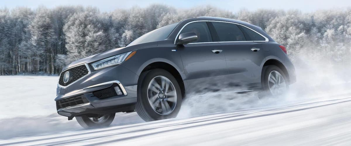 Low angle on Gray 2020 Acura MDX driving on snowy road
