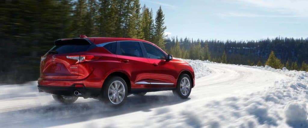 Red 2020 Acura RDX driving on snowy road with evergreen trees