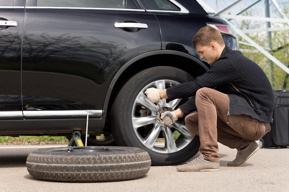 Young man changing the tire on a car