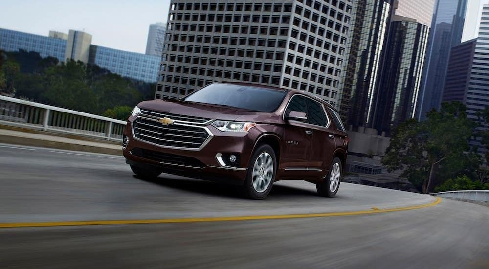 A maroon 2020 Chevy Traverse is driving on a highway away from a city.