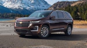 A burgundy 2022 Chevy Traverse is parked in front of mountains.
