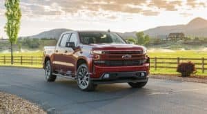 A red 2021 Chevy Silverado 1500 diesel is parked in front of a farm after leaving a Chevy Diesel Truck Dealer in Norfolk.