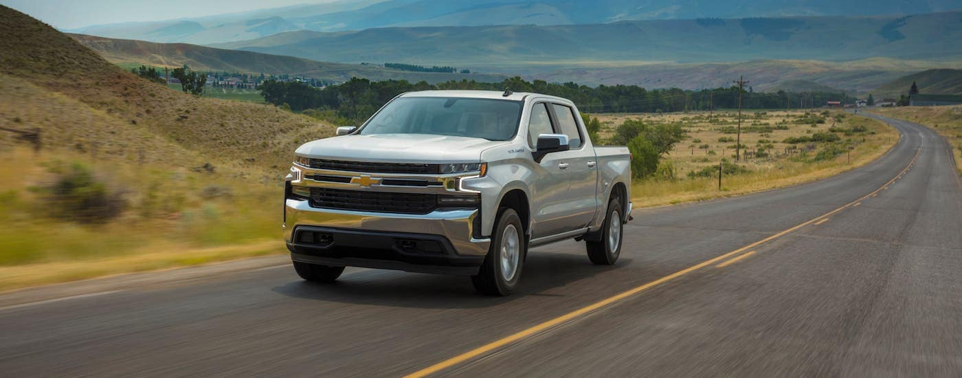 A silver 2020 Chevy Silverado 1500 LT is driving on an empty highway.