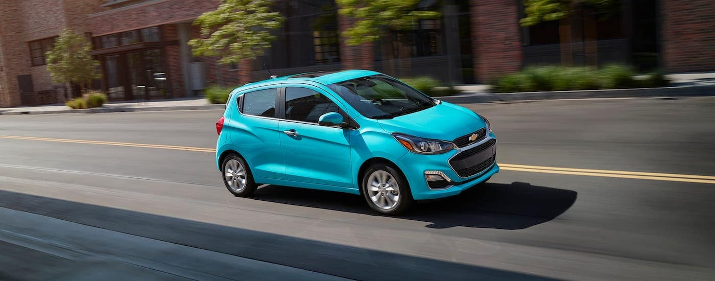 A teal 2021 Chevy Spark is driving on a city street.