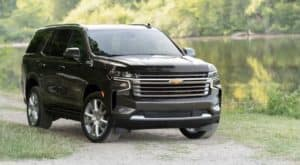A gray 2021 Chevy Tahoe High Country is parked in front of a pond after leaving a Hampton Chevy dealership.