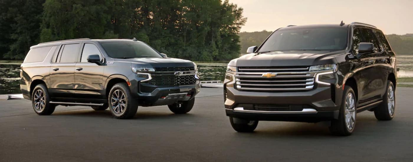 A black 2021 Chevy Suburban and a grey 2021 Tahoe are parked in front of a pond.
