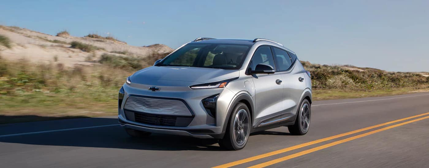 A silver 2022 Chevy Bolt EUV is driving past sand dunes after leaving a Chevy dealer in VA.
