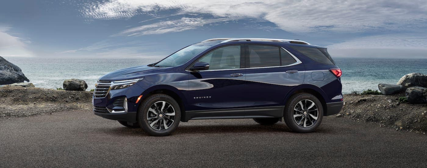 A blue 2022 Chevy Equinox is parked in front of a beach.