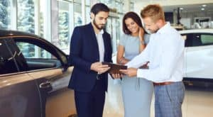 A salesman is looking at paperwork with a couple at a GMC dealer in Hampton Roads.