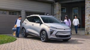 A family is in their driveway around a silver 2022 Chevy Bolt EUV.