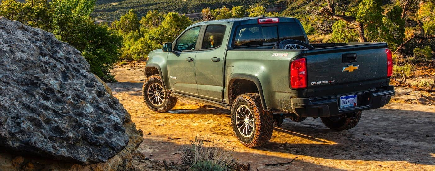 A green 2020 Chevy Colorado is shown from the back parked in the desert.