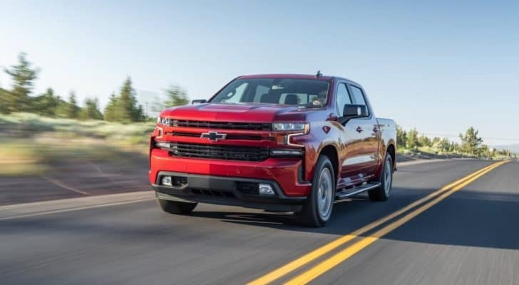 A red 2020 Chevy Silverado 1500 is driving down a two lane road after looking at pre-owned Chevy trucks.