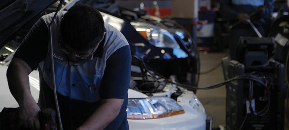 Honda technician working under hood of car
