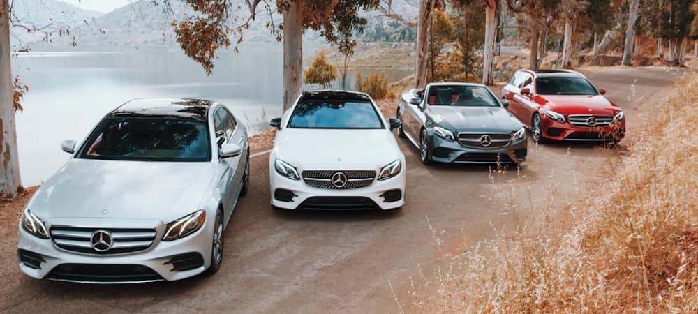 Four Mercedes-Benz E-Class models lined up along road