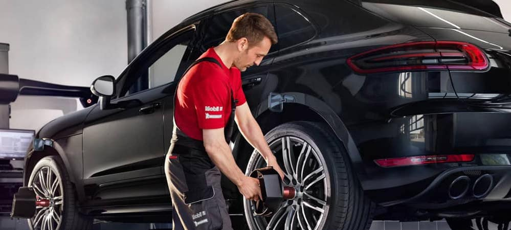 Mechanic servicing tires on a Porsche