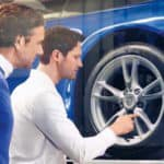 Service advisor and customer inspecting wheel