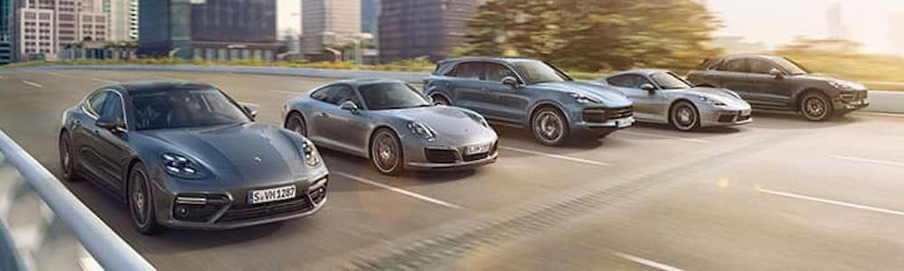 Porsche cars driving down city street