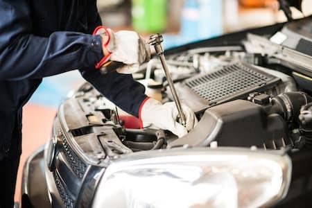 Technician utilizing tool to fix vehicle parts