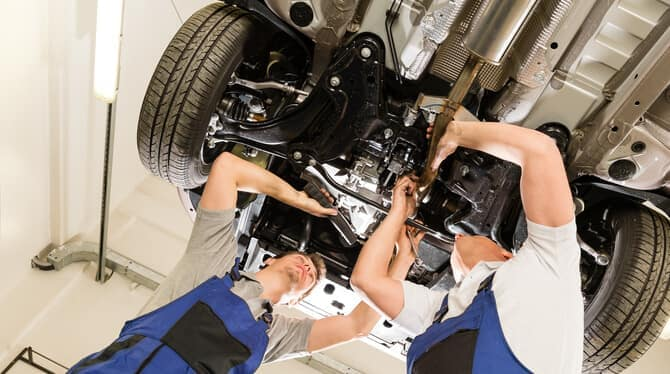 Two-mechanics-under-car-in-service-center