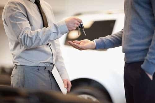 Man giving keys to another man