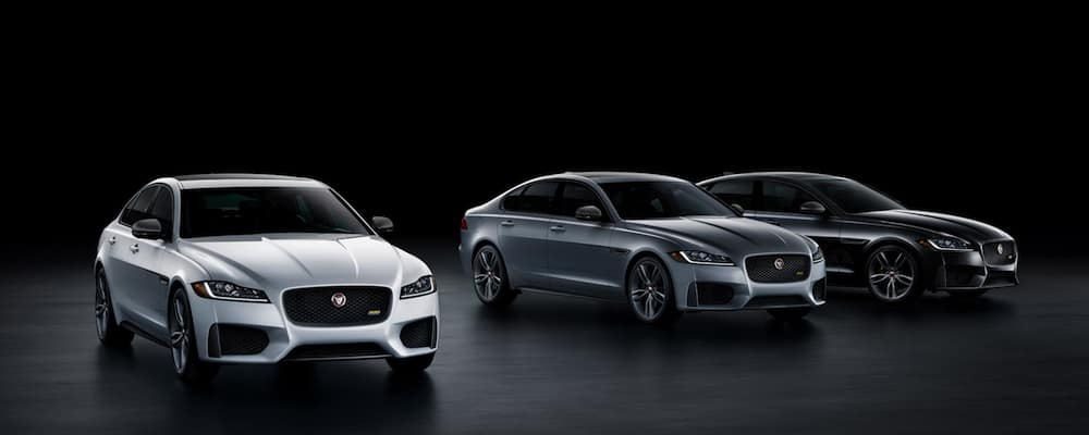 three xf sedans in silver gray and black against black backdrop