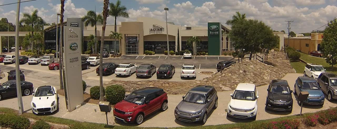 JAGUAR LAND ROVER DEALERSHIP WITH VEHICLES ON DISPLAY OUTSIDE.