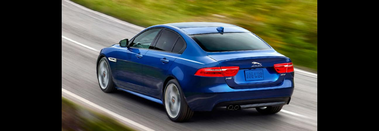Blue 2018 Jaguar XE speeding down the highway