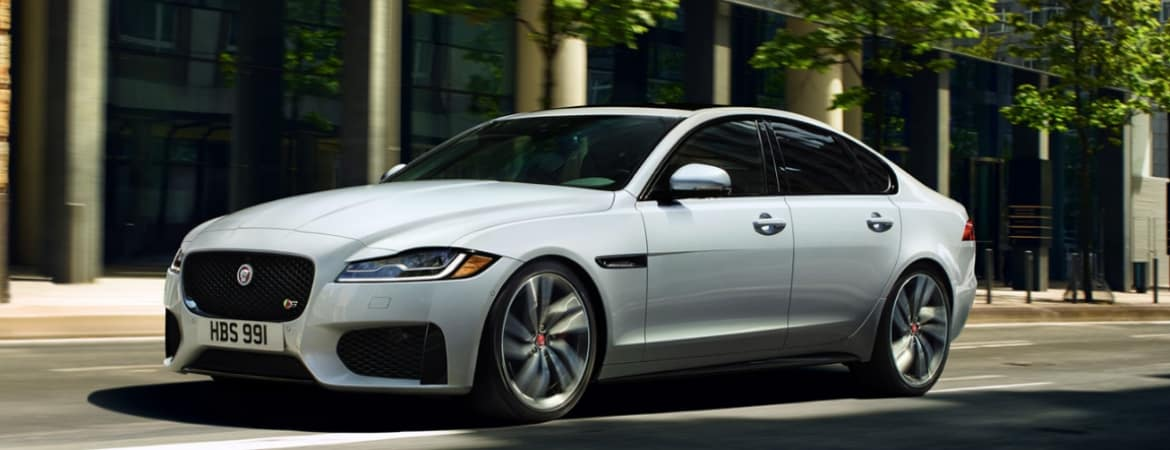 White 2019 Jaguar XF driving down the street
