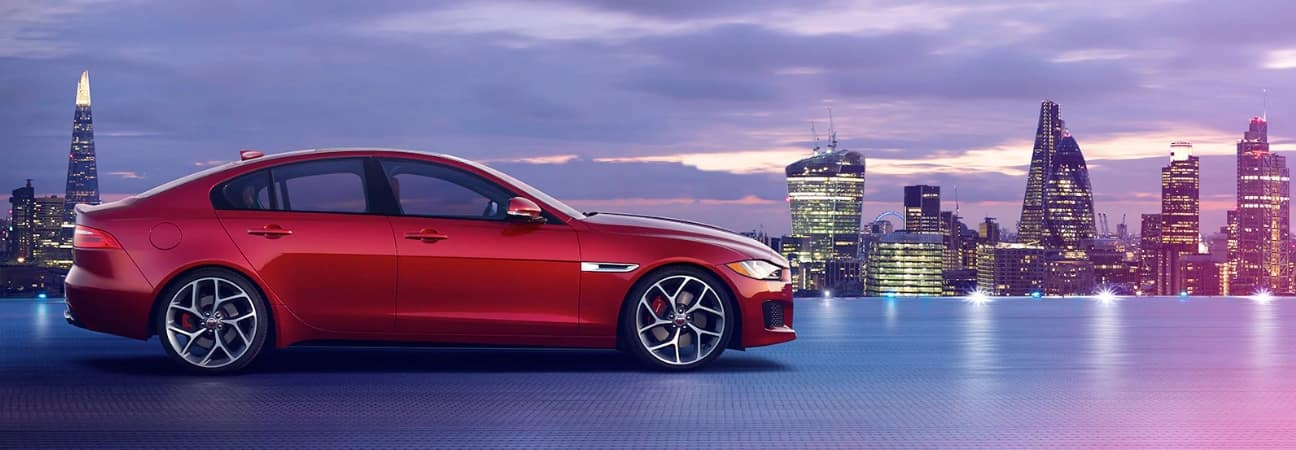 Red 2019 Jaguar XE in front of city skyline