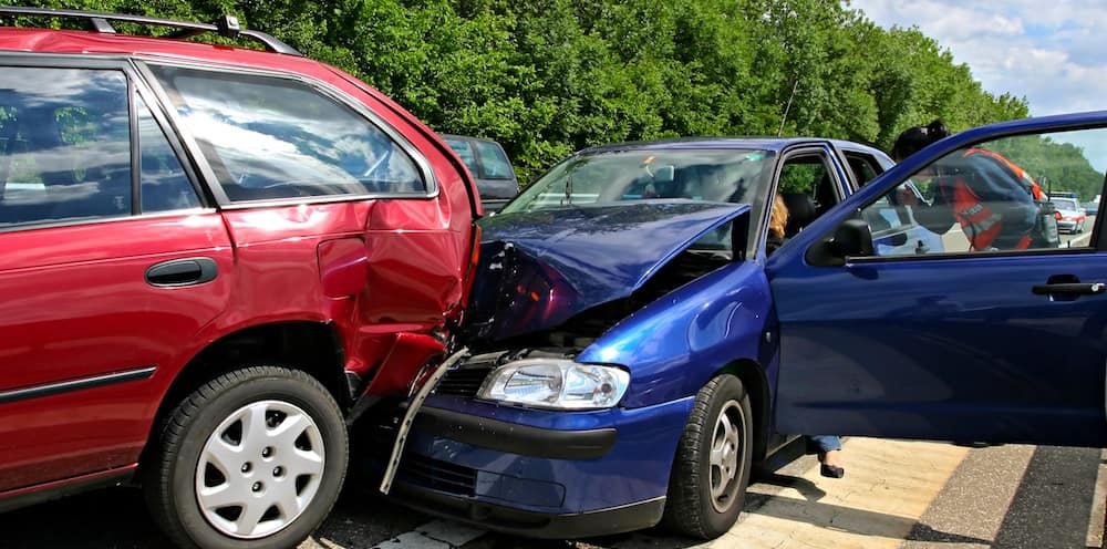 Blue sedan got into a rear-end collision with a red minivan
