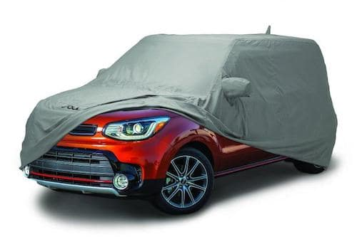 red Kia Soul with car cover over most of the vehicle