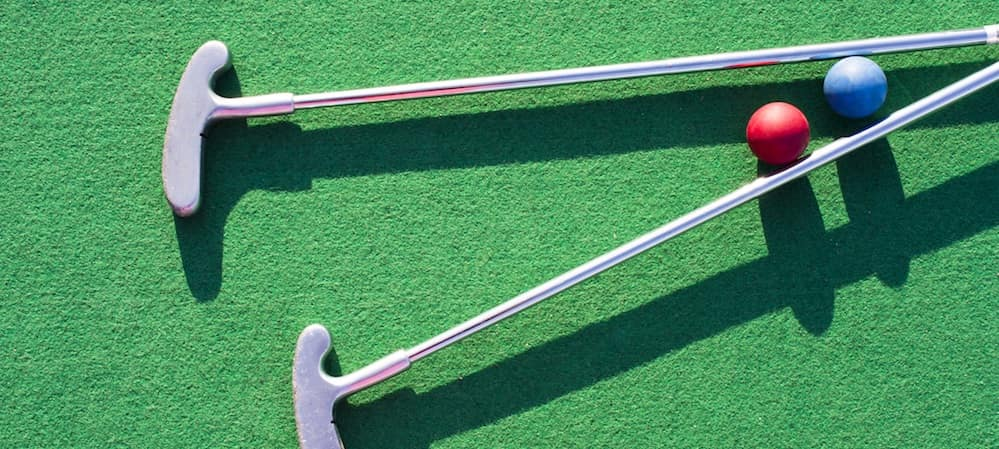 Two mini golf clubs and blue and red golf balls sitting on astroturf