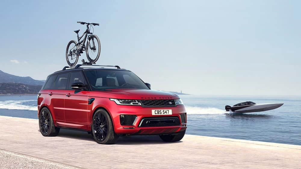 2018 Land Rover Range Rover parked in front of lake with bike on top rack